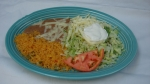 Tostada - A flat, crispy corn tortilla covered with beef, lettuce, cheese, tomatoes and sour cream. Served with rice and beans.